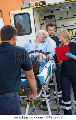 Paramedical team helping injured senior man lying on stretcher outdoors
