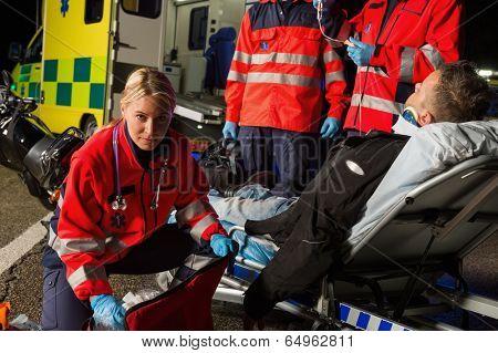 Paramedics assisting injured motorcycle man driver on stretcher at night