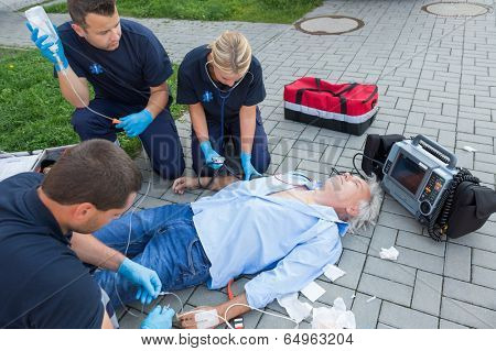 Emergency team giving firstaid to injured elderly patient on street