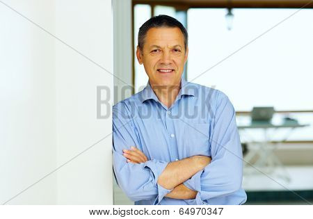 Happy Senior Man With Hands Folded at home