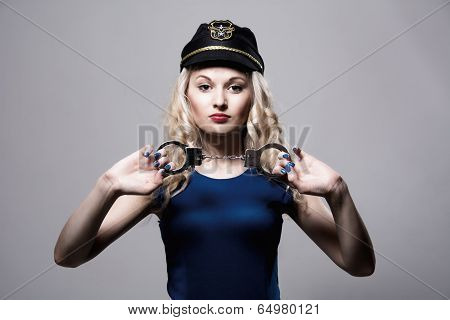 Beautiful Girl With Handcuffs And A Police Cap