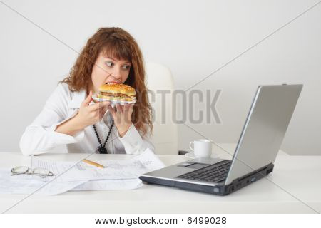 Person At Office On Workplace Eats A Hamburger
