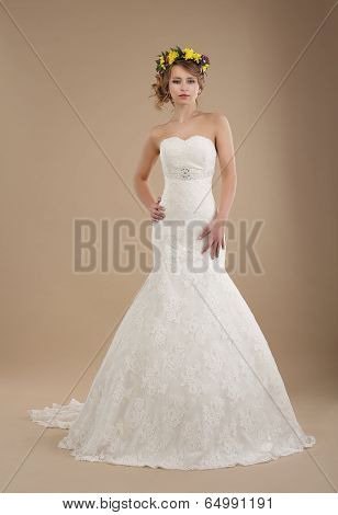 Charming Woman In Bridal Dress With Wreath Of Flowers