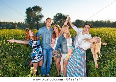 Group Of Happy Young People Posing In Rapeseed