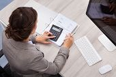 stock photo of calculator  - High Angle View Of Young Female Accountant Calculating Bills - JPG