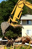 stock photo of track-hoe  - A large track hoe excavator tearing down an old hotel to make way for a new commercial development - JPG