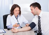 stock photo of hypertensive  - Female Doctor Checking Blood Pressure Of Young Businessman - JPG