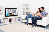 stock photo of watching movie  - Young Couple Sitting On Couch Watching Cookery Show - JPG