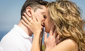 stock photo of kiss  - Passionate beautiful love couple kissing outdoors in a summer day over nature background - JPG