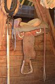 image of western saddle  - Old western saddle in a horse barn - JPG