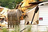 picture of track-hoe  - A large track hoe excavator tearing down an old hotel to make way for a new commercial development - JPG
