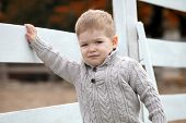 stock photo of baby cowboy  - 2 years old Baby boy on the a white picket fence beside the horse - JPG