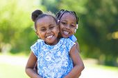 stock photo of cute innocent  - Outdoor portrait of a cute young black sisters laughing  - JPG