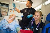 stock photo of paramedic  - Paramedical team treating unconscious elderly man on stretcher in ambulance - JPG