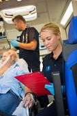 stock photo of stretcher  - Paramedic assisting injured senior patient on stretcher in ambulance - JPG