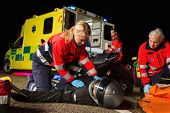 image of paramedic  - Paramedical team assisting injured man motorbike driver at night - JPG