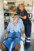 picture of stretcher  - Paramedical team treating unconscious senior patient lying on stretcher - JPG