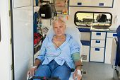 stock photo of stretcher  - Injured senior man sitting on stretcher in ambulance car - JPG