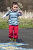 foto of hopscotch  - Child playing hopscotch game and jumping from number to number - JPG