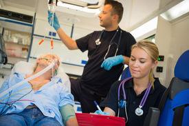 pic of ambulance  - Paramedical team treating unconscious elderly man on stretcher in ambulance - JPG