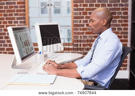 Side view of concentrated male photo editor using computer in the office