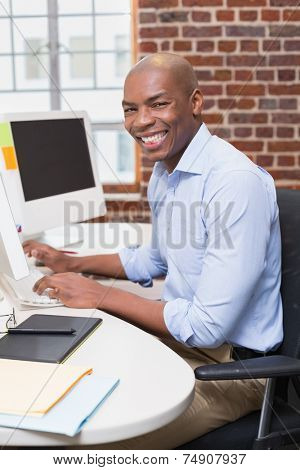 Portrait of young businessman using computer in the office