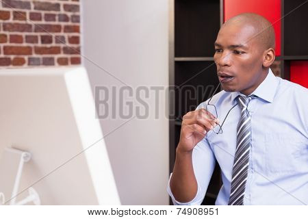 Serious young businessman looking at computer monitor in office