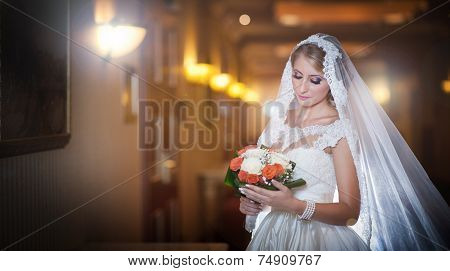 Young beautiful luxurious woman in wedding dress posing in luxurious interior. Bride with long veil