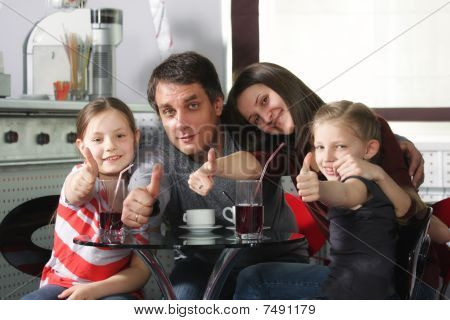 Family In Cafe Showing Thumbs Up