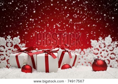 Christmas balls and gift boxes on snow over red background