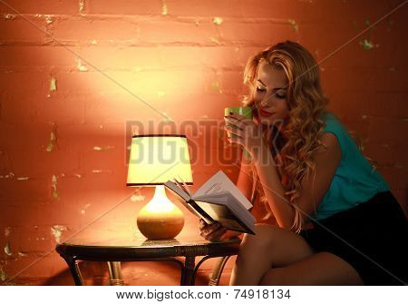 Beautiful Woman With Cup Of Coffee Reading A Book At Table In Cozy Cafe Home