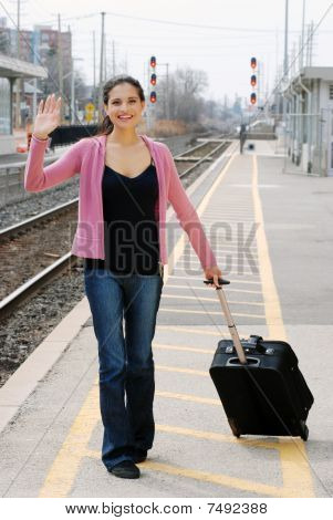 woman waving at train station