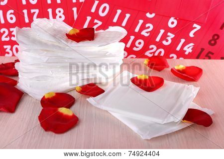 Sanitary pads and rose petals on wooden table on calendar background
