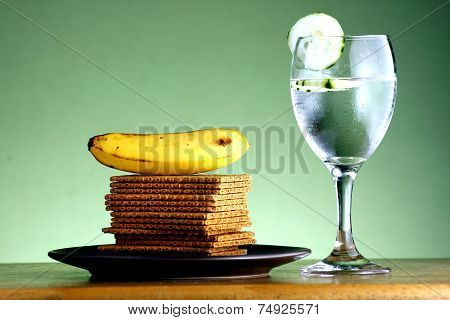 Stack of soda crackers, a banana and a goblet of water