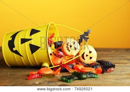 Different sweets for Halloween party on wooden table, on yellow background