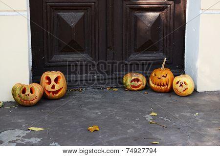 Pumpkins for holiday Halloween on old wooden door background