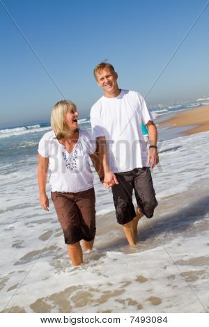 mature happy couple walking on beach
