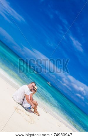 young loving couple relaxing on sand tropical beach on blue sky and sea background