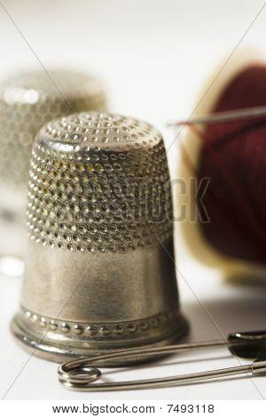 Thimbles, needle, thread and pin
