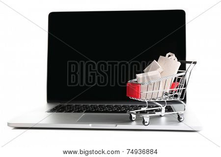 Shopping bags and boxes in shopping cart on laptop isolated on white