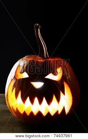 Halloween pumpkin on table on black background