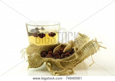 Cup of herbal tea with briar on a white background