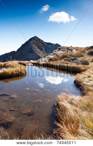 The north-est face of Mont Mucrone and a small mountain pond in a sunny autumn day. Biella, West italian Alps, Europe.