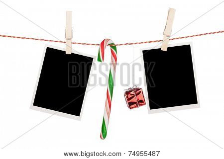 Blank photo frames and candy cane hanging on the clothesline. Isolated on white background
