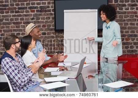 Young business team clapping hands in meeting at the office