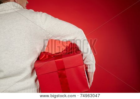 Man in white sweater holding big red giftbox in isolation