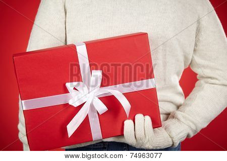 Man in white sweater and gloves hiding giftbox behind back