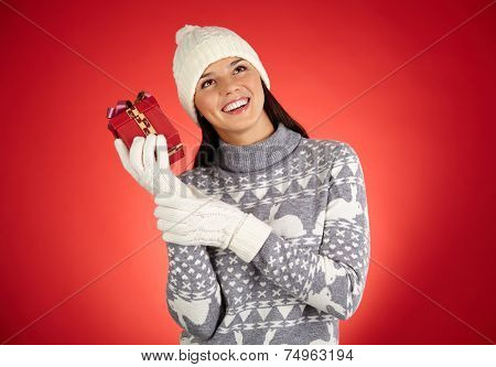 Portrait of ecstatic girl in winterwear trying to guess what is in giftbox