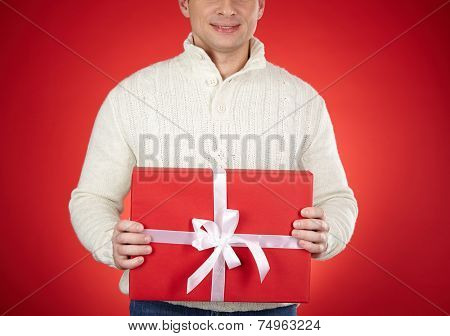 Smiling man in white sweater holding red giftbox tied with silk ribbon