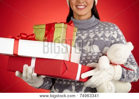 Smiling female in winterwear holding xmas packages and teddy bear